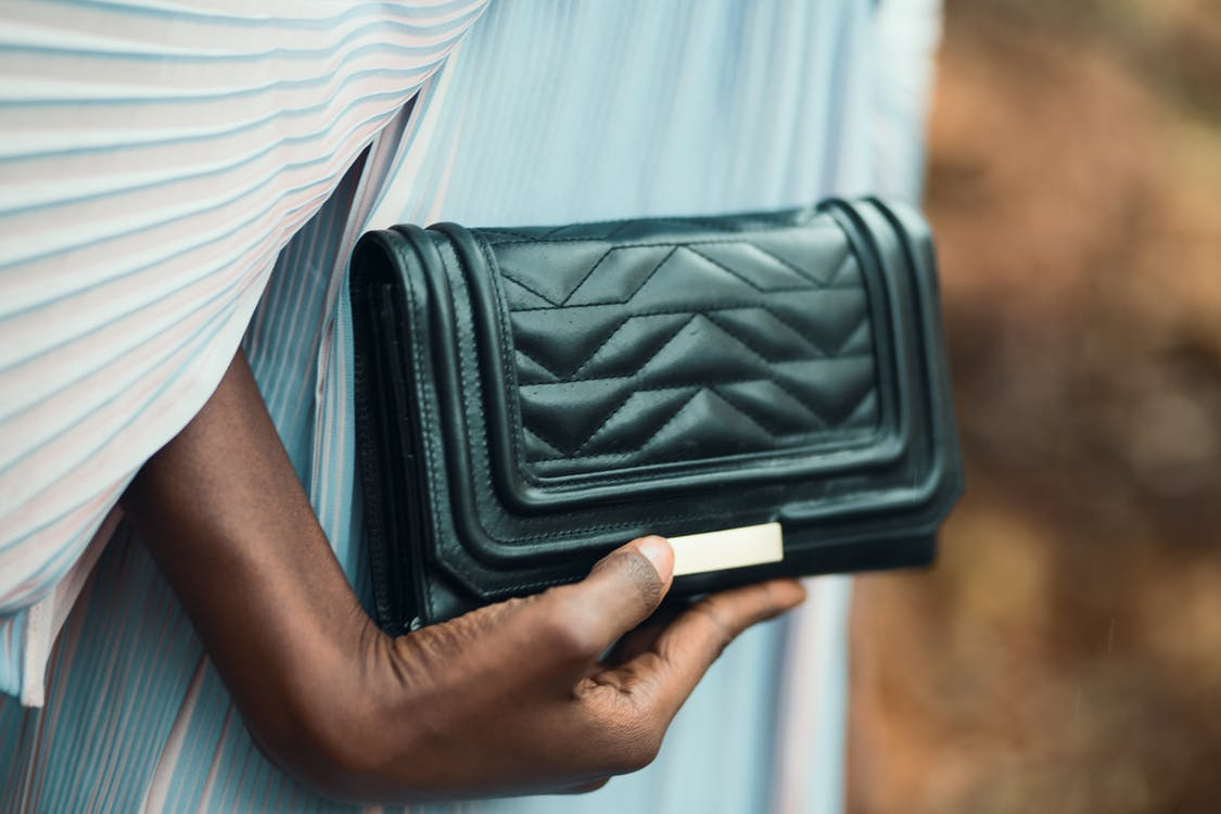 Person Holding Quilted Black Leather Clutch Bag
